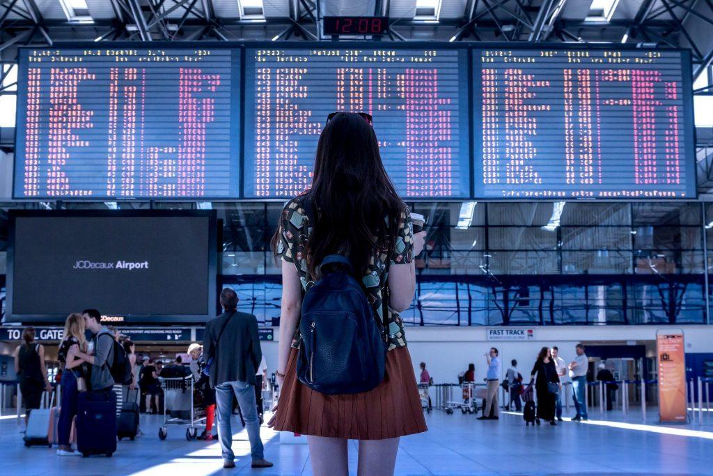 Girl watching departures board in airport